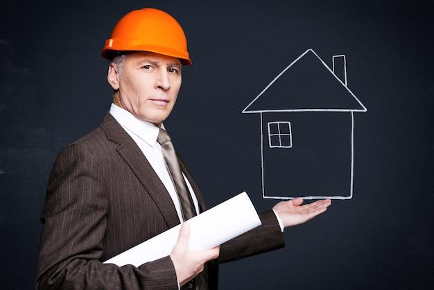 Architecte confiant. homme senior confiant en tenue de soirée et casque tenant une maison dessinée à la craie dans sa main et portant un plan tout en se tenant contre le tableau noir