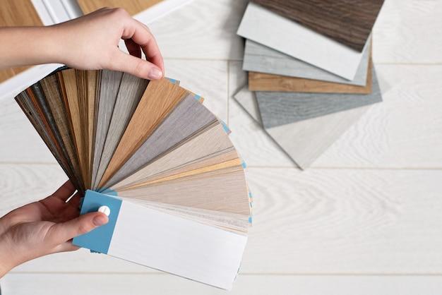 L'architecte designer détient une palette de textures et de décor pour un plancher en bois stratifié et vinyle. design d'intérieur. planification des réparations et de la construction de maisons.