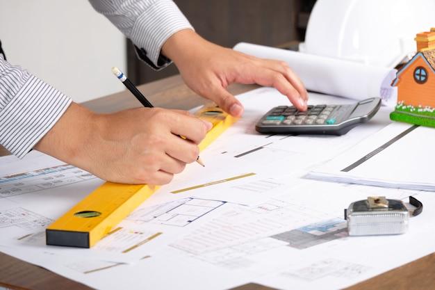 L'architecte dessine des plans de construction sur du papier blueprint avec un crayon et à l'aide d'une calculatrice.