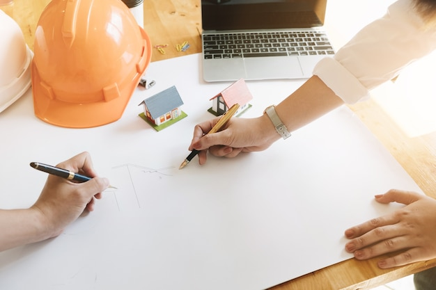 Architecte équipe à main levée dessin avec un stylo sur plan architectural en milieu de travail