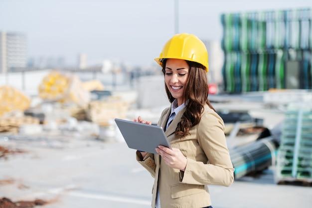 Architecte femme caucasien souriant attrayant en veste beige et avec un casque de protection sur la tête, debout sur le chantier de construction et à l'aide de tablette.