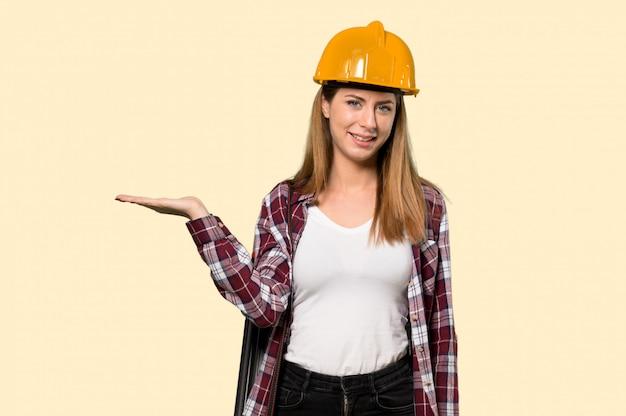 Architecte femme tenant une surface imaginaire sur la paume pour insérer une annonce sur un mur jaune isolé