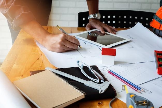 Architecte ou ingénieur à l'aide de stylo travaillant sur blueprint, concept architectural.
