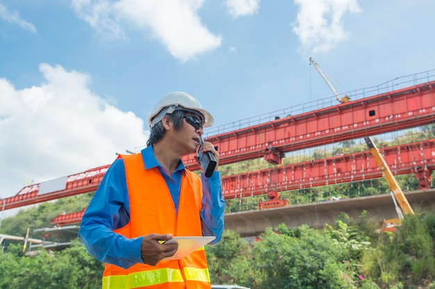 Architecte ou ingénieur, portant un casque blanc et un gilet de sécurité