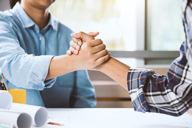 Architecte et ingénieur serrant la main au bureau. équipe de construction de concept travaillant sur le projet. la coopération