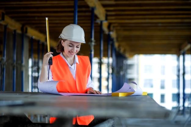Architecte ou ingénieur travaillant, parcourant le projet de construction à l'intérieur du chantier de construction avec plan directeur. femme ingénieurs en construction ou architectes qui travaillent.