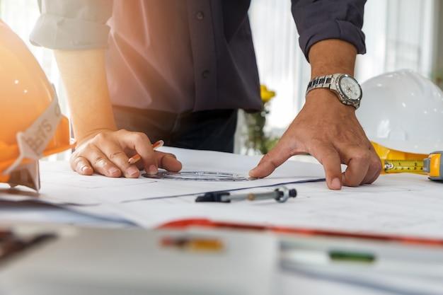 Architecte ou ingénieur utilisant un crayon et un rapporteur travaillant sur le plan.