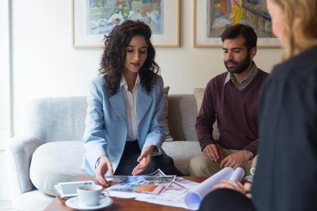 Architecte d'intérieur et clients discutant de dessins