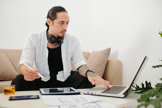 Architecte d'intérieur métis travaillant à domicile, il lit les courriels du client et vérifie les plans de construction