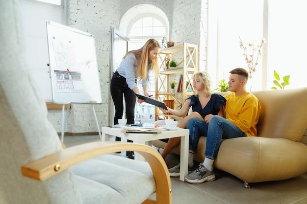 Architecte d'intérieur travaillant avec un jeune couple. belle famille et designer professionnel ou architecte discutant du concept de futur intérieur, travaillant avec une palette de couleurs, des dessins de pièce dans un bureau moderne.