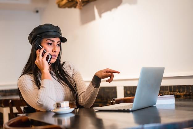 Architecte latina brune faisant un appel de travail avec un ordinateur portable dans un café