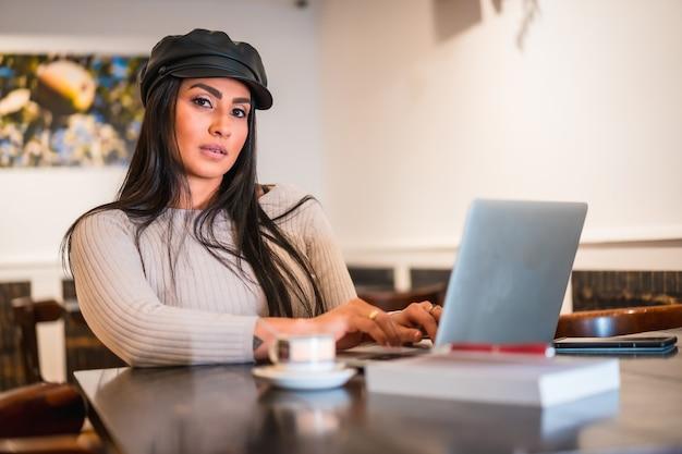 Architecte latina brune lisant des e-mails de travail avec le télétravail informatique depuis une cafétéria en vacances