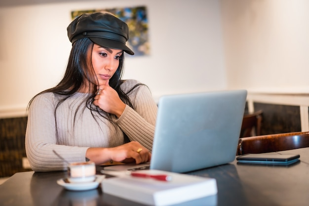 Architecte latina brune lisant des e-mails de travail avec le télétravail informatique depuis une cafétéria