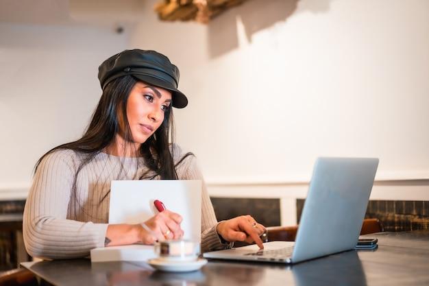 Architecte latina brune prenant des notes lors d'une réunion en ligne depuis un café