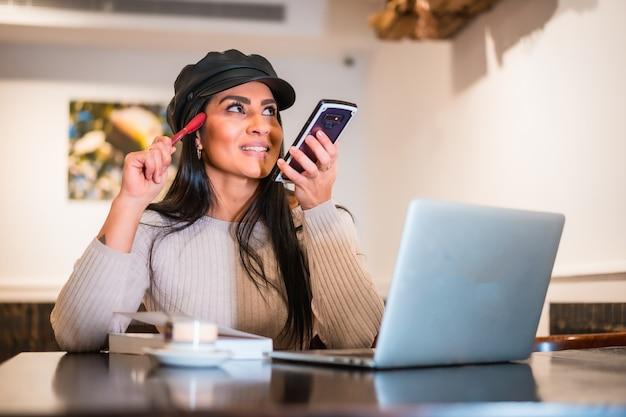 Architecte latina souriante envoyant une note audio de travail avec un téléphone portable depuis un café