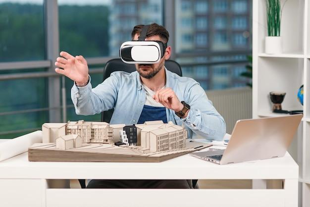Architecte masculin qualifié examinant un projet architectural avec des lunettes de réalité augmentée dans un bureau de design