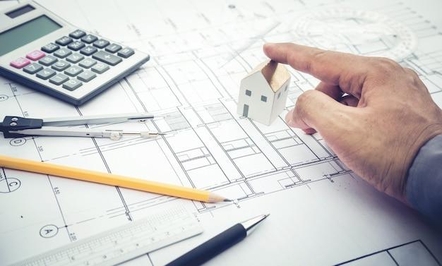 Architecte avec modèle de maison de centre commercial en main et conception de plan