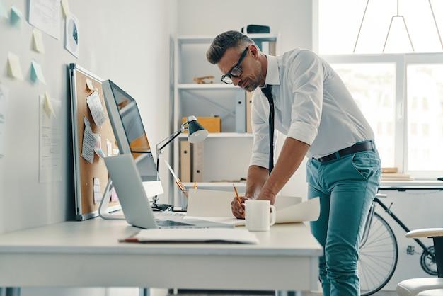 Architecte moderne. beau jeune homme dessinant quelque chose tout en travaillant au bureau