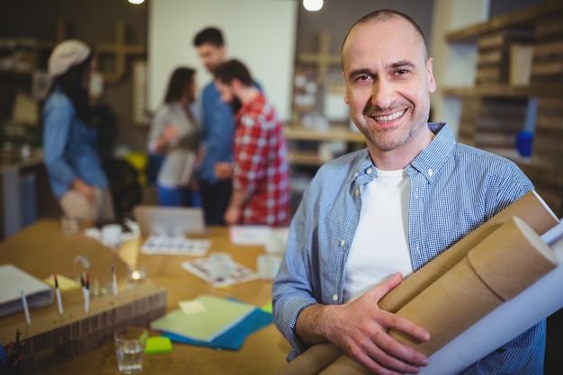 Architecte avec plans debout près de table