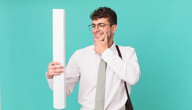 Architecte souriant avec une expression heureuse et confiante avec la main sur le menton, se demandant et regardant sur le côté