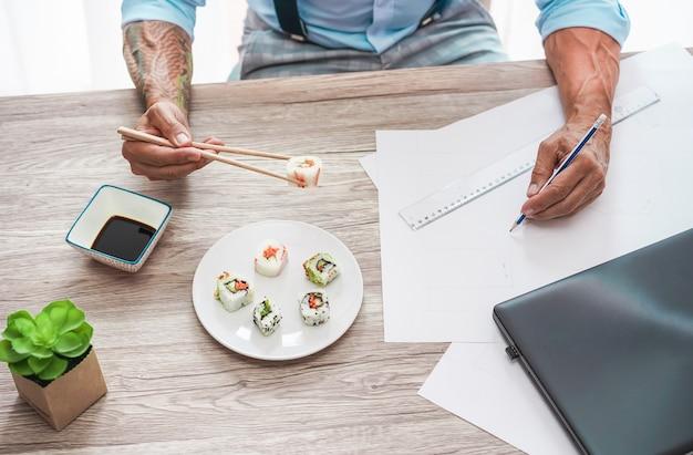 Architecte tatoué mangeant des sushis à l'heure du déjeuner tout en travaillant sur un nouveau projet