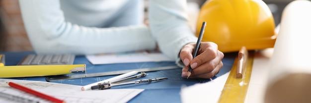 L'architecte tient un crayon dans ses mains et dessine le développement de croquis de la planification dans le bâtiment