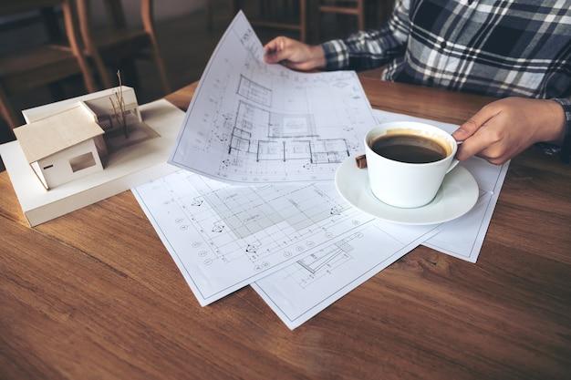 Un architecte travaillant sur un modèle d'architecture avec du papier d'atelier tout en buvant du café