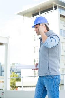 Architecte utilisant un téléphone portable à l'extérieur du bâtiment