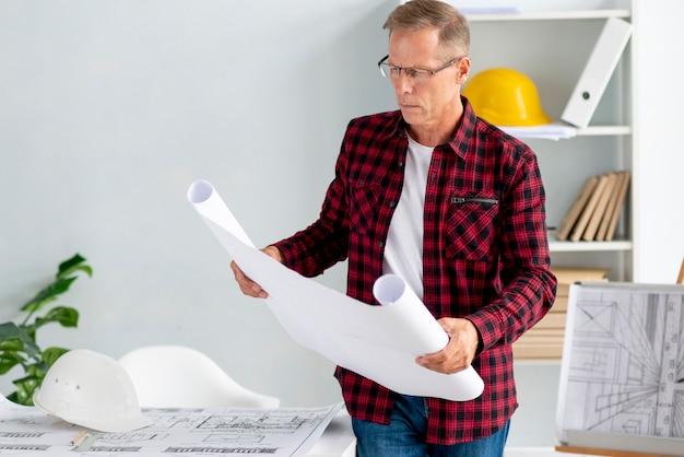 Architecte vérifiant le projet dans le bureau