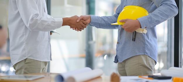 Les architectes et les entrepreneurs se serrent la main au travail.
