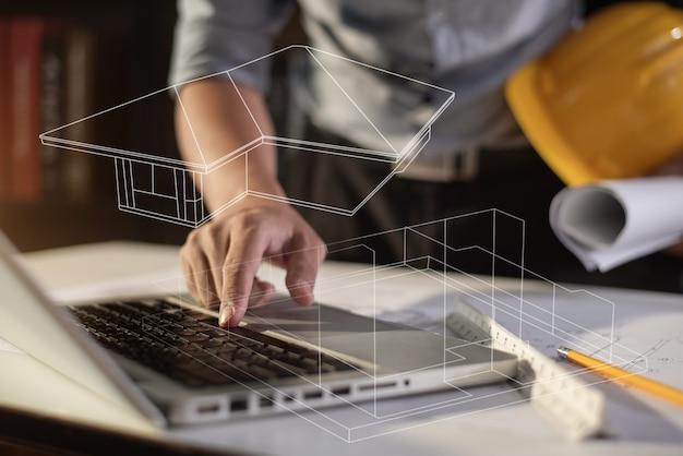 Architectes ou ingénieur tenant un stylo pointant des architectes d'équipement sur un ordinateur portable avec un projet architectural.