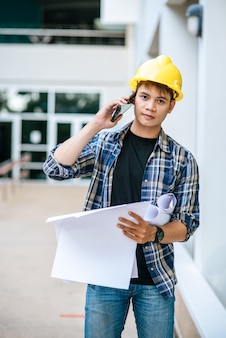 Les architectes tiennent des plans d'étage et parlent au téléphone.