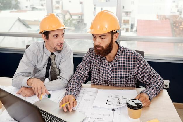 Architectes travaillant avec un ordinateur portable et un plan