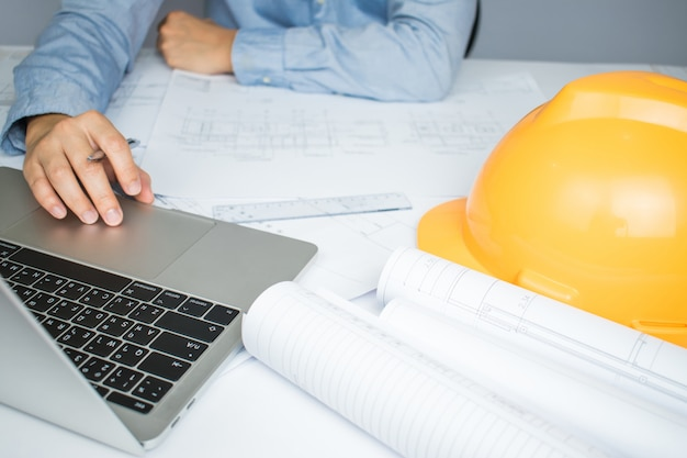 Les architectes utilisent beaucoup l'ordinateur portable pour obtenir des informations sur le papier blueprint posé sur la table.