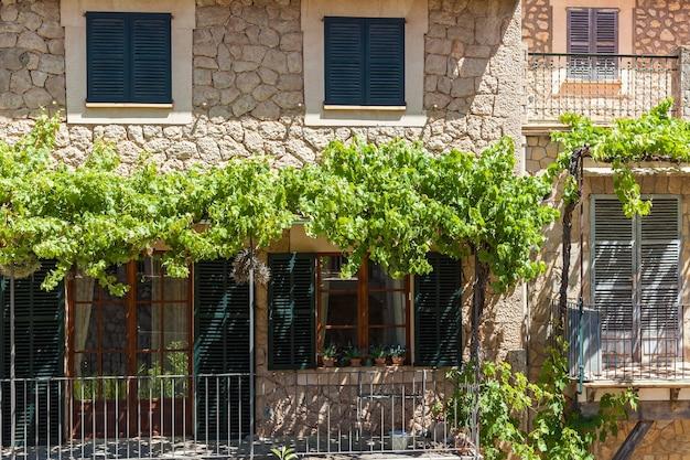 Architecture espagnole. jolie maison espagnole à deux étages en gros plan, balcon, entrée et plantes sur les rebords de la fenêtre.