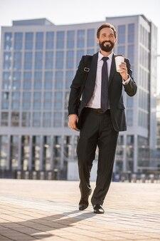 Architecture moderne. sur toute la longueur d'un joyeux bel homme d'affaires, boire du café à l'extérieur tout en se rendant au travail