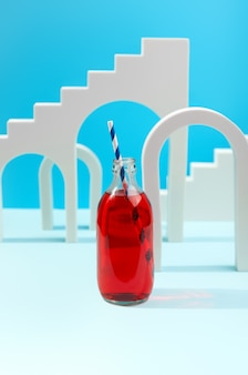 Arcs blancs sur fond bleu composition créative avec cocktail de limonade aux canneberges en bouteille