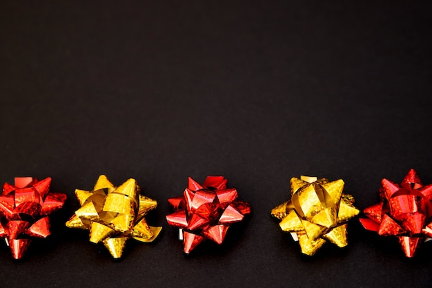 Les arcs de cadeau se trouvent dans une ligne sur un fond noir. noël et nouvel an. un cadeau d'anniversaire. espace vide pour le texte fond de vacances élégant.