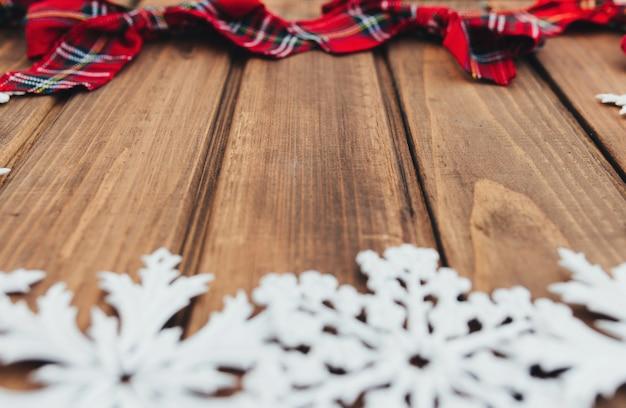 Arcs rouges de noël et flocons de neige blancs sur fond en bois marron. photo de haute qualité
