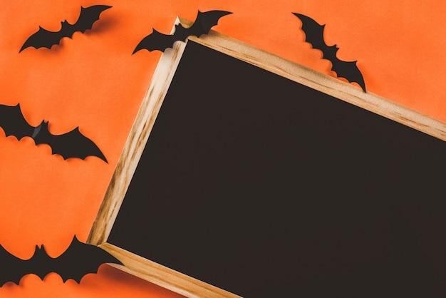 Ardoise ou ardoise à décorer avec des chauves-souris noires sur orange