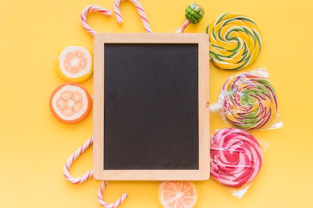 Ardoise en bois entourée de sucettes colorées et de bonbons de canne de noël sur fond jaune