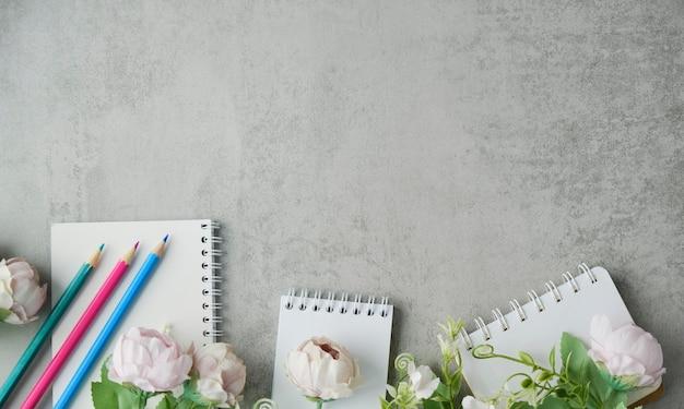 Ardoise décorée de pétales et de fleurs roses de pivoines sur un fond de béton gris avec