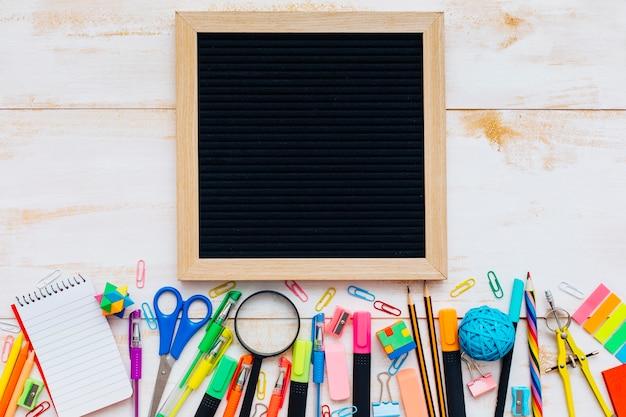 Ardoise avec des fournitures scolaires sur une table en bois