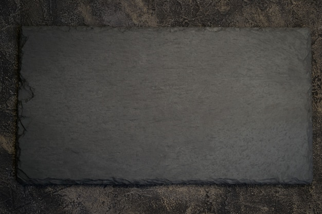 Ardoise noire sur fond de pierre sombre. vue de dessus avec copie s