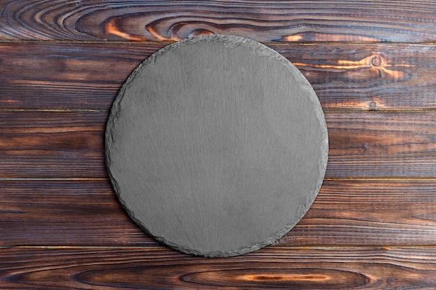 Ardoise ronde debout sur un bois, espace pour le texte
