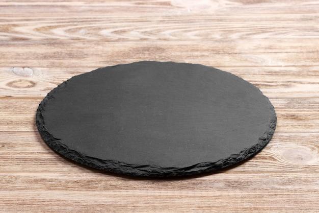 Ardoise ronde debout à bord d'un bois.