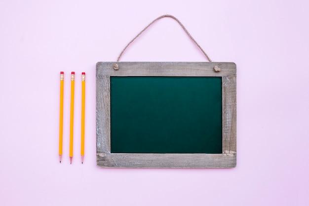 Ardoise scolaire avec trois crayons sur fond rose