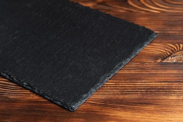 Ardoise de vaisselle, pierre noire sur fond de bois.