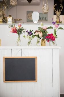 Ardoise vierge accrochée au mur avec de beaux vases à fleurs dans le magasin de fleurs