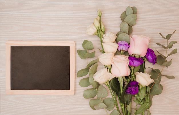 Ardoise vierge avec bouquet de fleurs sur fond en bois